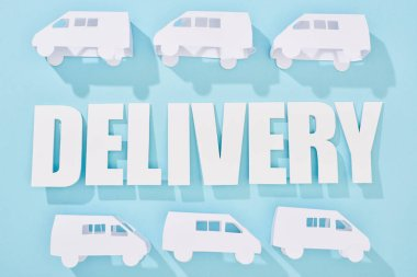 White mini vans around delivery inscription with shadows near blue background stock vector