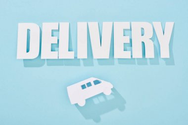 white delivery inscription with shadow above mini van on blue background
