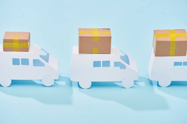 White mini vans with closed cardboard boxes on blue background stock vector