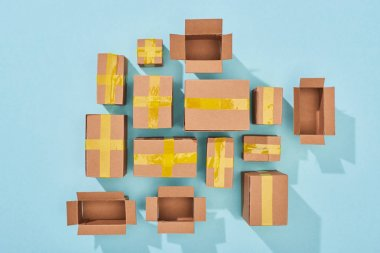 Top view of closed and open cardboard boxes on blue background stock vector