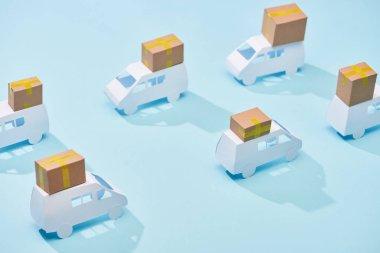 closed cardboard parcels on white mini vans on blue background