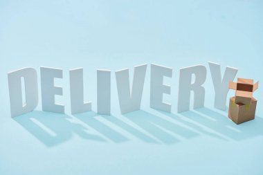 Cardboard boxes one on each other near white delivery inscription on blue background stock vector