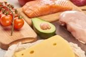 Fotografie Čerstvé surové ryby, drůbež, sýry, větve třešňových rajčat a půlka avokáda na dřevěných řezacích deskách