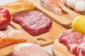 Čerstvé syrové maso, ryby, drůbež na dřevěných střihací prkně v blízkosti jablek, citrónu, bagety a vajec