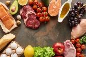 Pohled na syrové ryby, maso a drůbež v blízkosti zeleniny, ovoce, vajec, zeleně, bagety a olivového oleje na mramorový povrch s prostorem pro kopírování