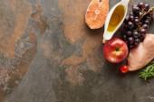 Felülnézet a nyers hal és baromfi közelében zöldségek, gyümölcsök, gyógynövény gallyak és olívaolaj márvány felületen a másolási tér