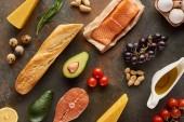 Felülnézet a nyers hal közelében zöldségek, gyümölcsök, tojás, sajt, földimogyoró, baguette és az olívaolaj márvány felületen