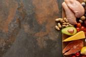 Vista dallalto del tagliere in legno con pesce crudo, pollame, formaggio, frutta, verdura, uova di quaglia, limone e arachidi sulla superficie marronisa scura con spazio di copia
