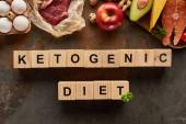Pohled na syrové maso a ryby v blízkosti vajíček, sýra, jablek, avokáda a podzemnice olejné na mramorové ploše s dřevěnou krychlí ketogenní diety