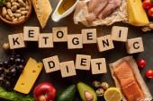 Pohled na surovou drůbež a ryby v blízkosti vajec, sýra, ovoce, zeleniny, bagety, podzemnice olejné a olivového oleje na mramorové ploše s dřevěnými kostek ketogenní diety