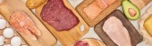 Panoramic shot raw meat, fish and poultry on wooden cutting boards near chicken eggs and half of avocado