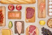 Pohled na rozmanité maso, drůbež, ryby, vejce, ovoce, zeleninu, sýry a bagetu na dřevěné řezací desky na povrchu mramoru