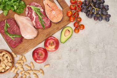 Top view of assorted meat, poultry and fish with greenery on wooden cutting board near apples, grapes, peanuts, cherry tomatoes and half of avocado on gray marble surface