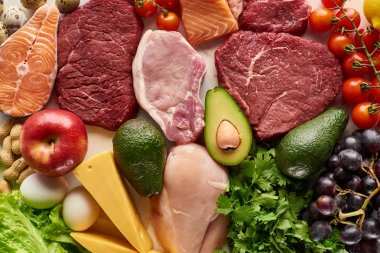 Top view of assorted raw meat, poultry, fish, eggs, vegetables, fruits, nuts, greenery and cheese