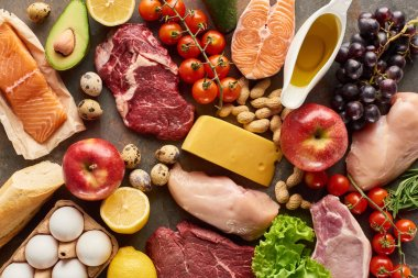 Top view of assorted meat, poultry, fish, eggs, fruits, vegetables, cheese, olive oil and baguette
