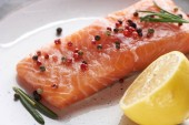 close up view of raw fresh salmon with pepper, lemon and rosemary on plate