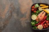 Nejlepší pohled na surový čerstvý losos se zeleninou, citronem a bylinami v pánvi na grilu