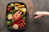 Photo partial view of woman holding raw salmon with vegetables, lemon and herbs in grill pan