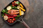 Fotografie Nejlepší pohled na surový losos se zeleninou, citronem a bylinami v pánvi na grilu