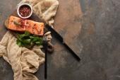 pohled na surový čerstvý losos s peppercorny, petržel na dřevěné řezací desce blízko příborů a hadříku