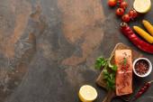 felülnézet nyers friss lazac, fűszerek, fa vágódeszka közelében zöldség és citrom
