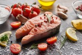raw salmon steak with seasoning and tomatoes on stone board