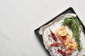 top view of raw salmon steak with lemon, rosemary and chili peppers on oven tray with salt