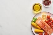 vista dallalto della bistecca di salmone crudo con mais e pomodori su piatto vicino olio e grani di pepe sul tavolo di marmo