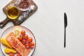 felülnézet a nyers lazac steak kukoricával és paradicsommal a tányéron közel késsel és fa vágódeszka a márvány asztalon