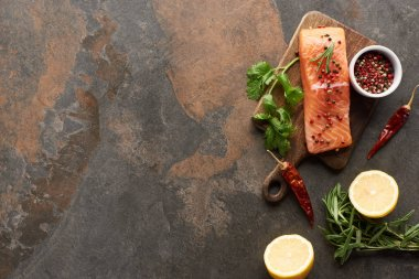 top view of raw fresh salmon with greenery, chili peppers and lemon on wooden cutting board