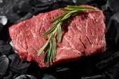 zblízka pohled na steak ze surového hovězího masa s rozmarýzvětvičem na charálech