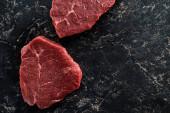 Fotografie Draufsicht auf ungekochte Rinderlenden auf schwarzem Marmorhintergrund