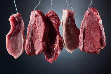 Assorted raw meat steaks on metal hooks on dark black background stock vector