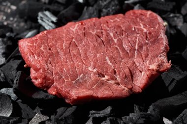Close up view of raw sirloin on black charcoal pieces stock vector
