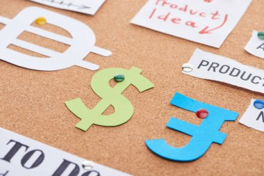 color paper cards with currency signs pinned on cork office board