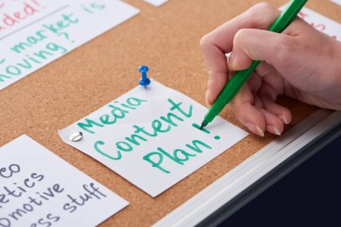 cropped view of woman writing media content plan inscription on card pinned on cork board
