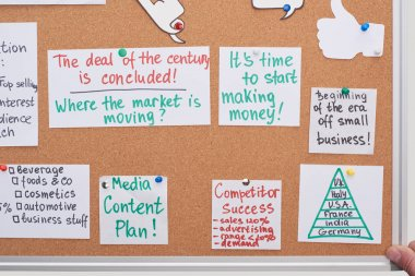top view of cards with work plan notes pinned on office cork board