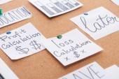 papírové karty se záznamy o výpočtech zisků a ztrát připojené k kancelářské desce