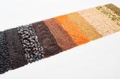 schwarze Bohnen, Reis, Quinoa, Kichererbsen, Kürbiskerne, Buchweizen, Mais und rote Linsen isoliert auf weiß