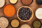 Schalen mit Bohnen, weißem Reis, rotem Linsen, Couscous und Buchweizen und Kichererbsen auf Holzoberfläche