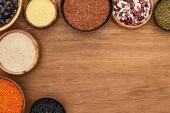 Fotografie Schalen von oben mit verschiedenen Bohnen, roten Linsen, Couscous und Buchweizen auf Holzoberfläche