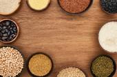 Draufsicht auf Schalen mit Bohnen, weißem Reis, Couscous und Buchweizen und Kichererbsen auf Holzoberfläche