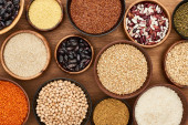 Photo top view of bowls with whole grains and legumes on wooden surface