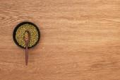 Draufsicht auf Schüssel mit Mondbohnen mit Löffel auf Holzoberfläche