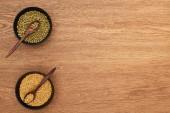Fotografie Draufsicht auf Schalen mit Mondbohnen und Weizen mit Löffeln auf Holzoberfläche