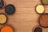 Schüsseln mit Quinoa, Couscous, Bohnen, Kichererbsen und Linsen auf Holzoberfläche