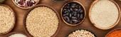 Fotografie Panoramaaufnahme von Schalen mit Haferflocken, Buchweizen, Quinoa, Bohnen und Kichererbsen auf Holzoberfläche