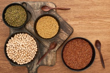 top view of bowls with moong beans, chickpea and cereals on wooden cutting boards with spoons