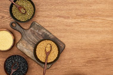 top view of cutting board with bowls with black beans, maash, couscous and buckwheat on wooden surface