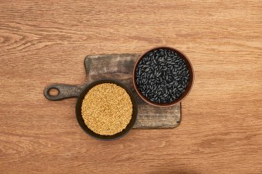 top view of bowls with beans and grains on wooden cutting board